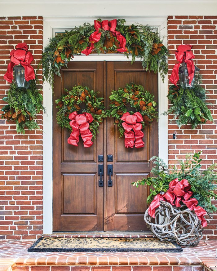 A grand set of natural wood doors on a brick on, with a wreath on each door, bundles of greenery on lantern, an arch of greenery over the doorway. To the side of the door, Canaan Marshall also adorned a grapevine sculpture with greenery. Large red bows finish each decorative element.