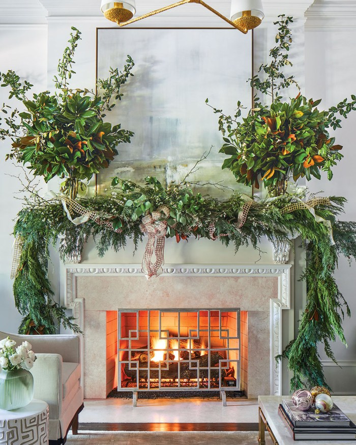 lush garland and two large vases of greenery, with ribbon accents, decorate a holiday mantel