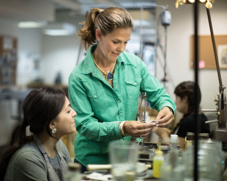 Clara Williams, wearing a green button-up with her hair pulled into a jaunty ponytail, at work in her design studio