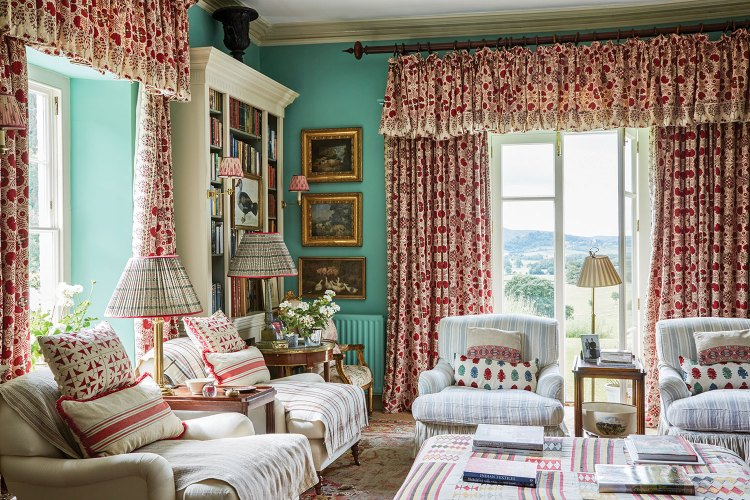 The aqua wall color contrasts with the muted reds featured prominently in various prints on the draperies and throw pillows. Comfortable reading chairs wear soft white upholstery and slipcovers with a pale stripe pattern