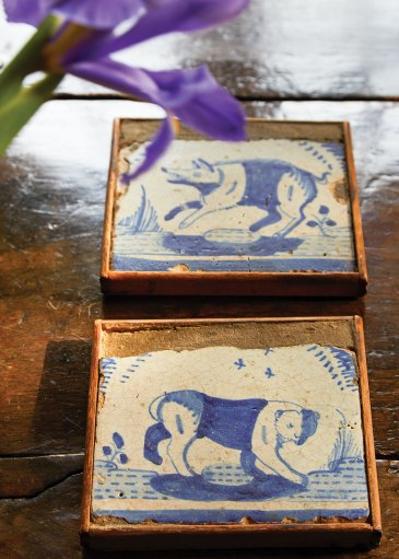 The age-worn pair of blue-and-white tiles, which depict a bear and a wolf, are displayed in thin individual frames set on a glossy wood plank surface in the book 'Near & Far' by Lisa Fine