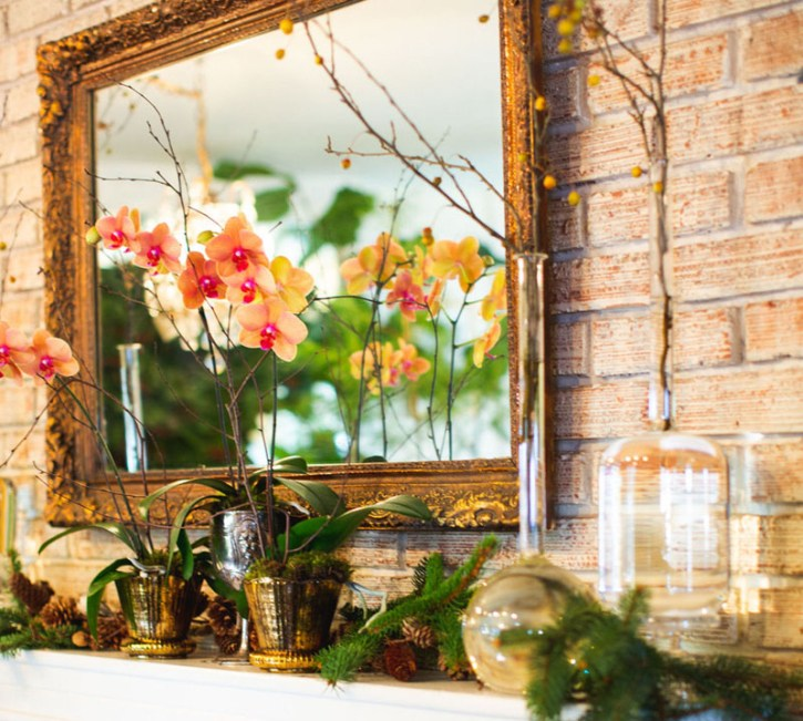 Potted orchids, branches of berries displayed in vintage glass bottles, and evergreen clippings on a mantel beneath a gilt antique mirror