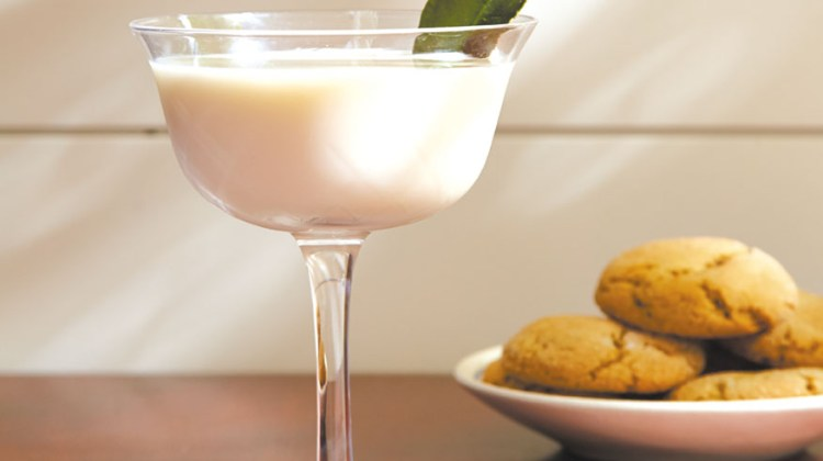 A creamy white gin-based cocktail garnished with a lime leaf next to a plate of ginger snap cookies