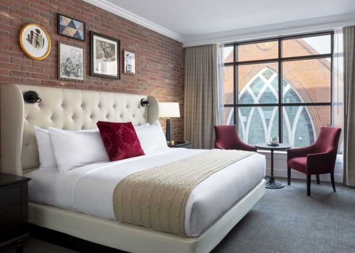 Best hotels in Asheville: A room at The Foundry, featuring exposed brick walls and a view looking onto a large stained glass window of a church in downtown Asheville