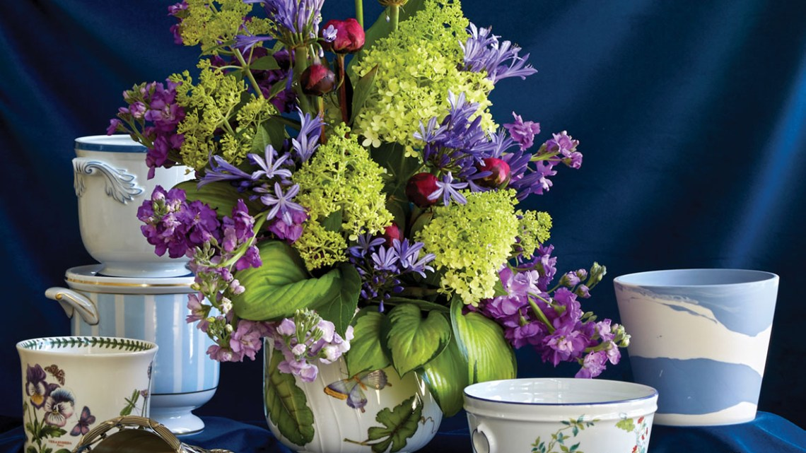 A collection of cachepot, with a vibrant purple and green floral arrangement filling one of the vessels in the center, against a dark blue velvet backdrop