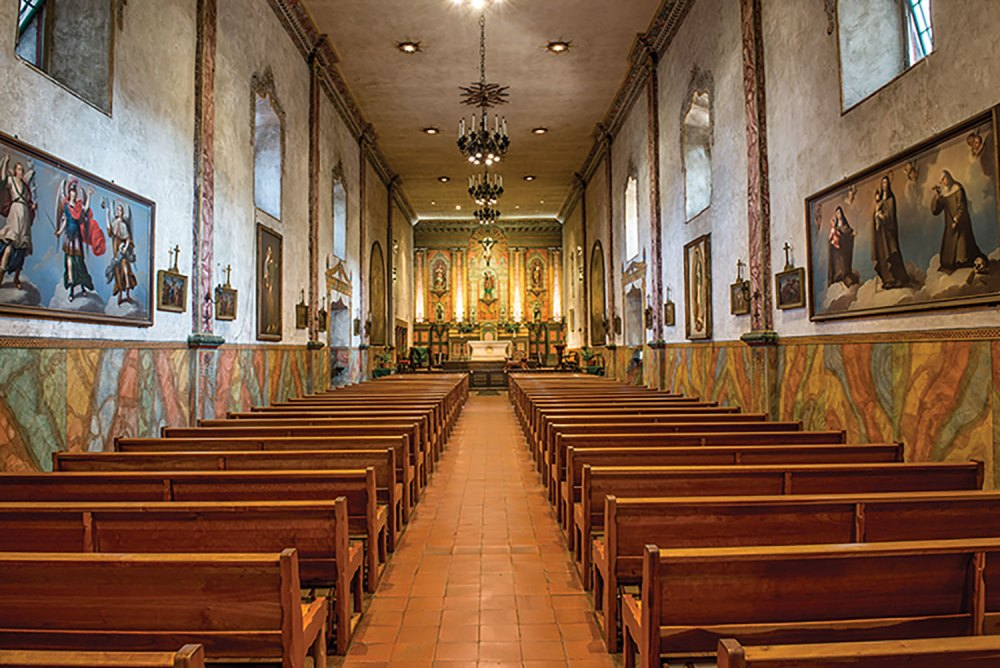 View of Old Santa Barbara Mission sanctuary, with red tile floors, natural wood pews, and art hung all long the stucco walls beneath high, deep windows