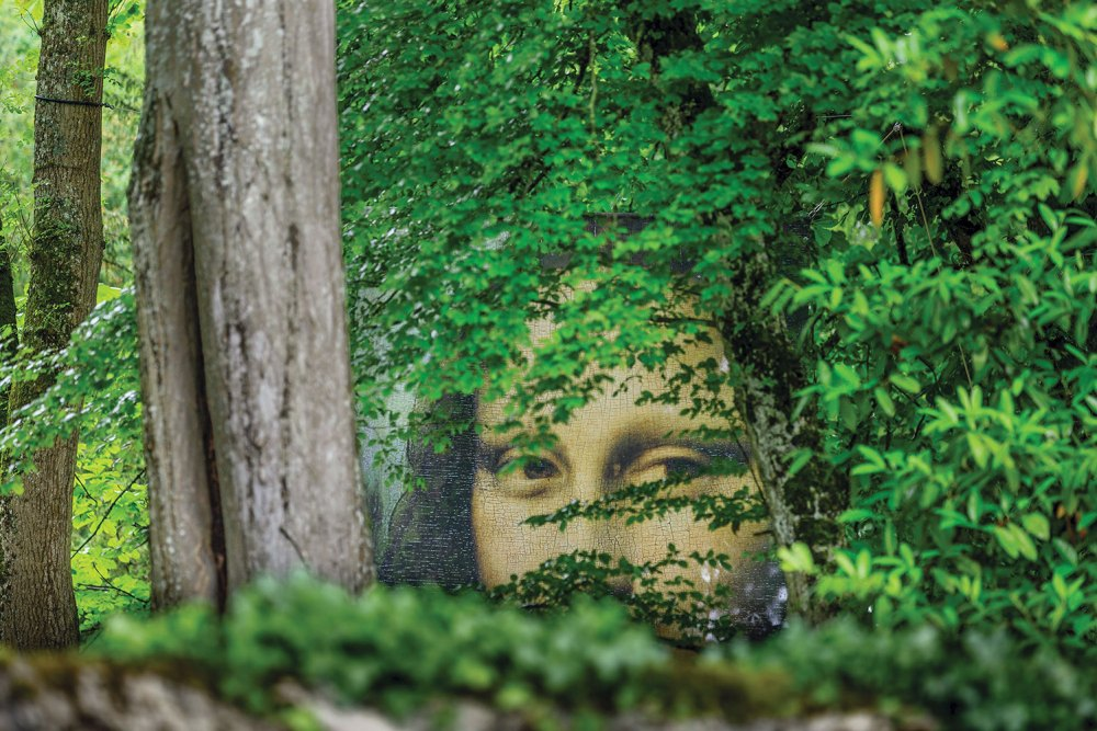 A large mural of the Mona Lisa peers through the trees in the In the Leonardo da Vinci Park in the Loire Valley