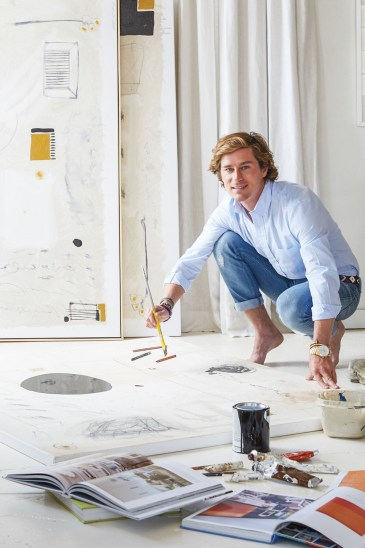 Interior designer and artist William McLure dressed in jeans and button up leans with rolled up sleeves leans over a painting-in-progress, brush in hand.