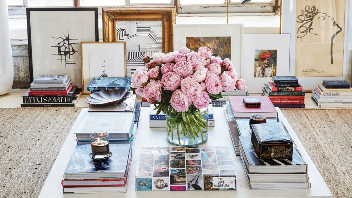 William McLure art and interiors: A large white square coffee table, with stacks of coffee table books on art and design and a vase of lush pink blooms at the center. Framed art is propped against the wall in the background