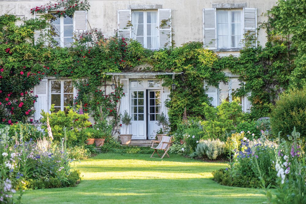 Exterior view of Sharon Santoni 's home in France, partially covered in climbing vines, and opening onto a stretch of lawn with a curving garden beds on either side