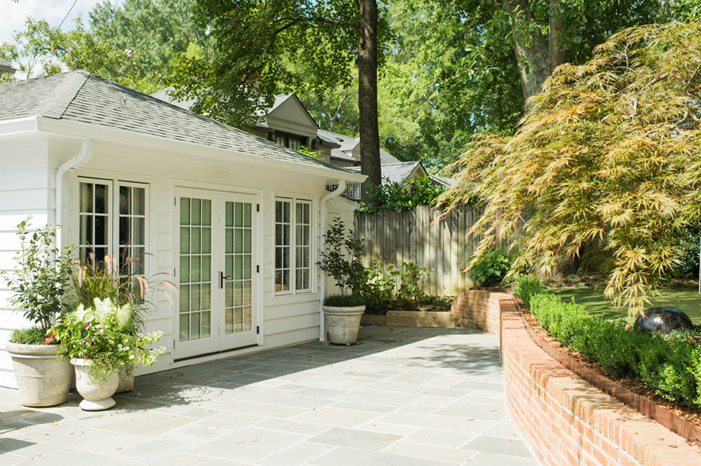 A quaint home with white siding illustrates places that need outdoor spring cleaning and maintenance, windows, doors, eaves, patios, and garden containers