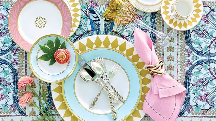 A spring table setting features cool shades of blue and pink, elevated by the symmetry of gold harlequin china sitting atop a fetching lyrebird patterned tablecloth.