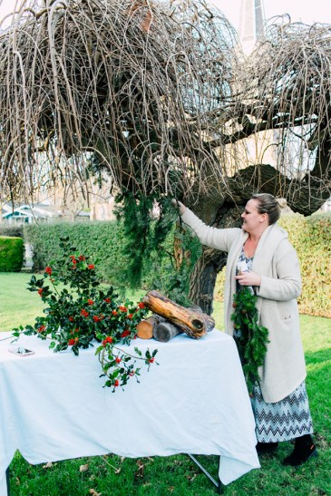 Floral designer Natalie Ransom hangs foraged evergreen foliage on a bare tree. Underneath, a table is decorated with holly branches.
