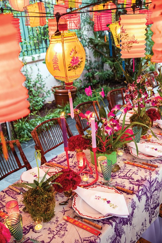 A Chinoiserie-themed party designed by Rebecca Gardner features glowing vintage Chinese lanterns, orchids, and a chinoiserie tablecloth