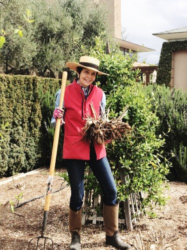 Frances Schultz, wearing a brimmed hat, red vest, jeans, and boots, stands in her garden, hoe in hand