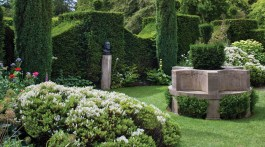 The Cottage Garden with a circular stone seat and bust, Highgrove Garden, June 2011.