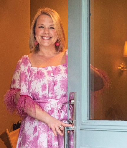 Rebecca Gardner greets party guests at the front door of a Savannah, Georgia, home. She wears a pink and white floral dress. The door is painted pale turquoise and features a large frosted window in the top half.