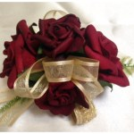 Burgundy roses, gold ribbon.
