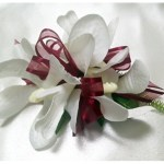 Orchids with burgundy organza ribbon.