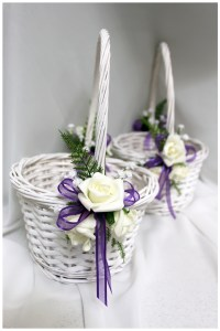 Flower girl baskets with purple organza ribbon, white roses,baby's breath and greenery.
