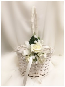 White flower girl basket. Cream satin ribbon handle and bows, white roses, rose leaves, fine fern and baby's breath.
