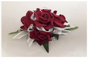 Deep red rose wrist corsage, white ribbon with silver thread, diamantes added.
