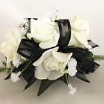 White roses, black organza ribbon, added baby's breath.