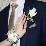 White rose corsage, ivory with gold thread ribbon, gold diamante wristband and matching buttonhole with bow.