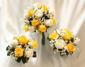 Bridal posy with flower girl posies using yellow and white roses and baby's breath.