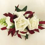 White roses with thin burgundy satin ribbon.