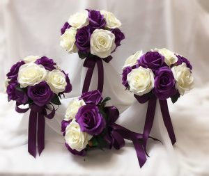 Purple and white open rose posies for bridesmaids.
