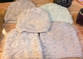Knitted hats in several styles, beige and off-white