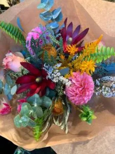 This hand-tied bouquet has hot pink dahlias, red leucadendron, pink roses, banksia protea, pink celosia and white triptemene with sword fern and blue eucalyptus.