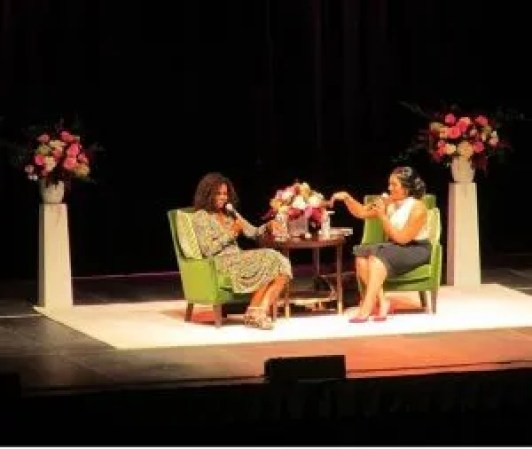 Komal Minhas interviewing Michelle Obama on stage beside floral arrangements