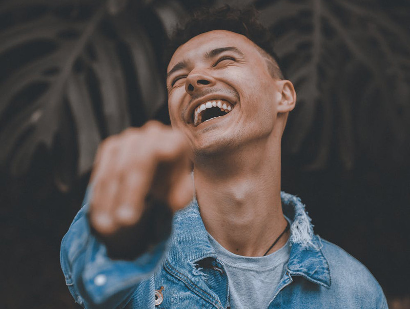 Man laughing and pointing at the camera