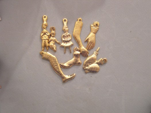 "Small metal ""milagros""-examples of a leg, foot, hands, children, and an arm."