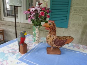 These very different birds come from rural areas of Central America, where I bought each of them. The bird on the left is a species of trogan, large, colorful birds of the tropics, bought in Costa Rica. The chicken came from Guatemala.