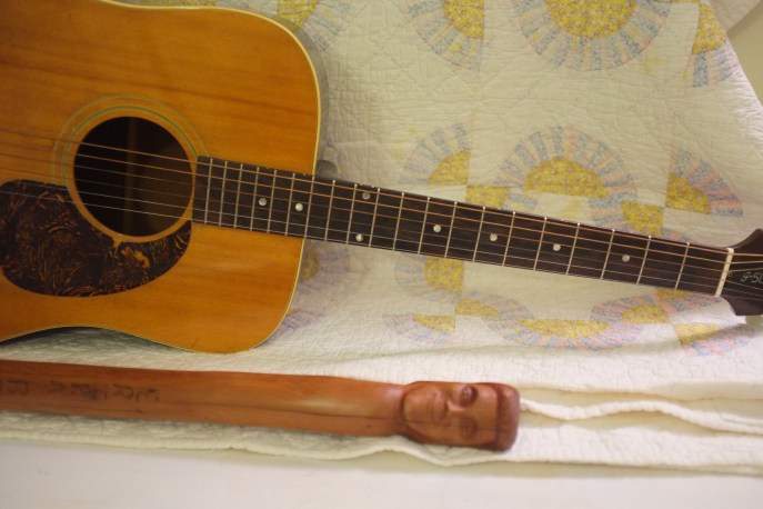 1968 Gibson J-50 formerly belonging to National Heritage Fellowship awardee Eddie Pennington, along with carved cedar walking-stick with head depicting stylized Erika Brady and carved inscription on the shaft. Gifts of Eddie Pennington honoring our long and blessed friendship.