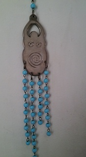 This combination of Old World Evil Eye blue beads and a modern Goddess spirituality figure (with raised arms, breasts and a spiral on the belly) shows both the adaptation of an old form to a new belief system, and the borrowing (and/or appropriation?) of old folk magical practices by the modern Pagan or New Age spirituality movements.