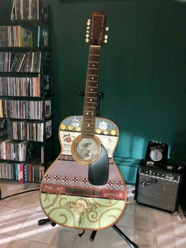 """I bought this piece for ten dollars at a yard sale in Atwater Village, CA in 2016. The couple who sold this to me told me they had bought it in a raffle (or auction…I can't remember which) for a substantially higher price at a festival in Telluride Colorado. I don't know the year. All I know is that Johnny Cash's pensive songwriting face is enshrined inside the sound hole, and the lyrics to his """"I Still Miss Someone"""" (co-written by Johnny Cash and his nephew Roy Cash JR) are reprinted across the body. While this piece is not signed, the artist explains the imagery in a note pasted on the back which reads, """"THEY HAVE $$$ BUT THEY DON'T HAVE CASH - The song written is """"I Still Miss Someone from Mr. Johnny Cash. I feel the sheriff badges sum up his time on top, the dog bones sum up his low down ways, and the dice, a roll of what kind of man he was that day. The title is a line from a Darrell Scott song."""""""