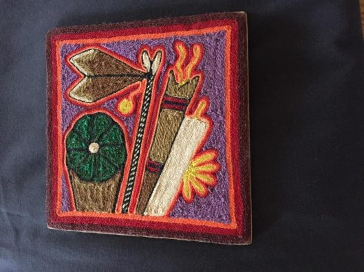 "Huichol yarn art often represents sacred objects. The back of this piece states, ""Aqui vemos ofrendas dedicados al peyote, y todas estas ofrendas son llevados a su lugar sagrado, en Wirikuta."" By Teresa Renteria. English translation: ""Here we see offerings dedicated to peyote, and all these offerings are taken to their sacred place, in Wirikuta."" The Huichol people live in the Sierra Madre in four states in Mexico: Jalisco, Nayarit, Durango, and Zacatecas. Often called ""shamanistic art,"" the yarn paintings may include feathered wands, peyote, snakes, the white-tailed deer, and other visionary objects seen on the artist's vision quest taken when an initiate. The desert of Wirikuta is where the dawn first appeared and the world was created."