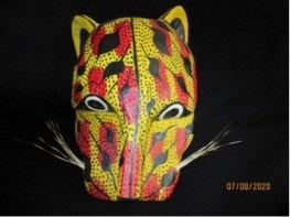 Hand carved wood though solid, not hollowed out in the back. 8 x 6 inches, painted in yellow and red, with black dots and stripes. Whiskers are the stiff hairs from a natural source, possibly an animal. Somewhat asymmetrical. The Jaguar is indigenous to Mexico but also echoes the people's Native background, where deities appeared as a frightful Jaguar. He is a favorite character who tires to frighten the Shepherds on their quest for Baby Jesus.