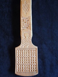 Bottom half of an unusual milk spoon, with the 9 squares on the bowl each divided into 9 more squares, hence a total of 81 squares for the milk, thus increasing its spiritual power when the milk is tossed from the spoon. The lower part of the handle (shown) depicts the Buddhist Eternal Knot and protective swastika symbols, as well as the sun rising over the mountains of Mongolia. Carvings on the upper part (not shown) include clouds, a zodiac symbol, and a horse's head. Purchased: Countryside east of Ulaanbaatar, Mongolia, 2018. Material: Wood. Dimensions: 16-1/4 inches long.