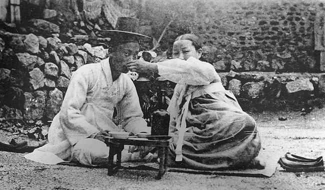 A gisaeng feeding alcohol to a country yangban.