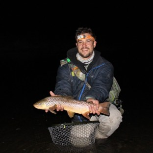 Adam Ross night fishing holding a trophy brown.