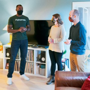 A Flyhomes real estate agent showing a home to a couple in their early thirties