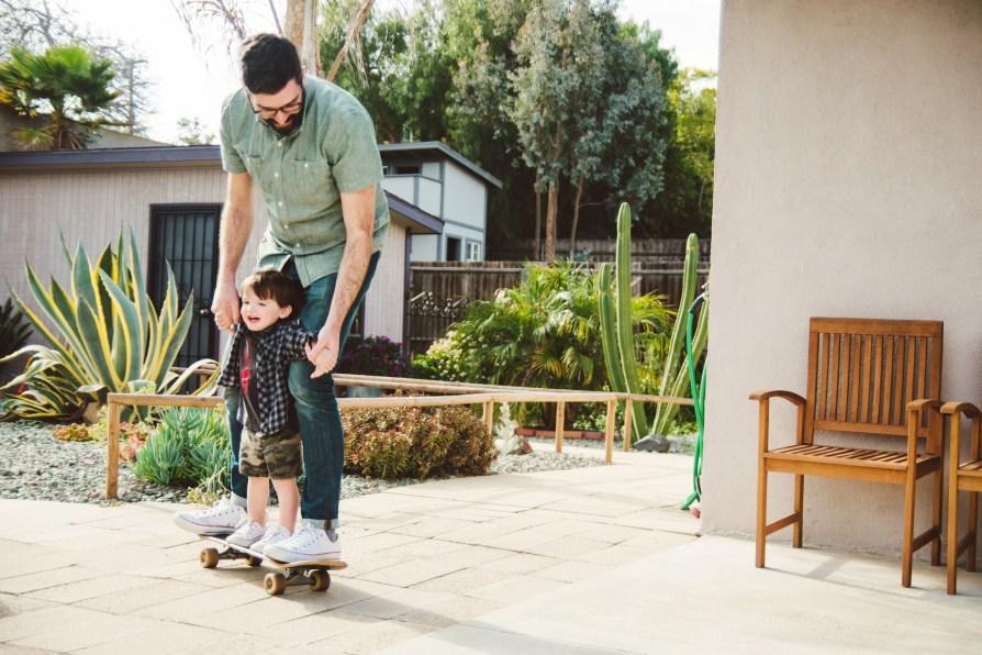 Man helping boy on skateboard