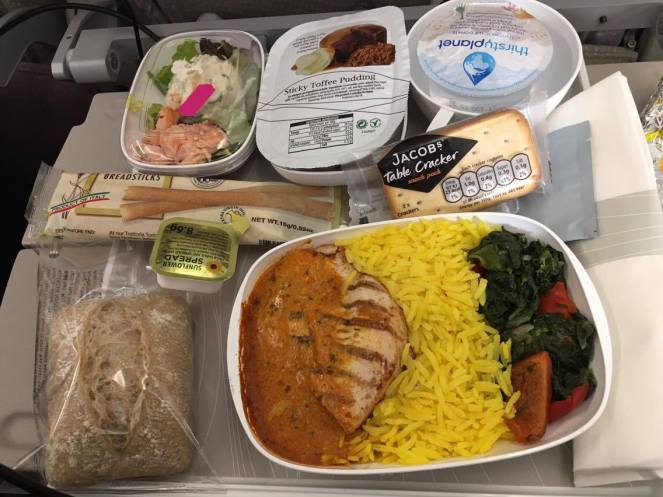 Emirates economy food with bread roll, sunflower spread, breadsticks, Jacob's Table Crackers, chicken curry with yellow rice and vegetables, a sticky toffee pudding and a thirstyplanet water on a grey tray