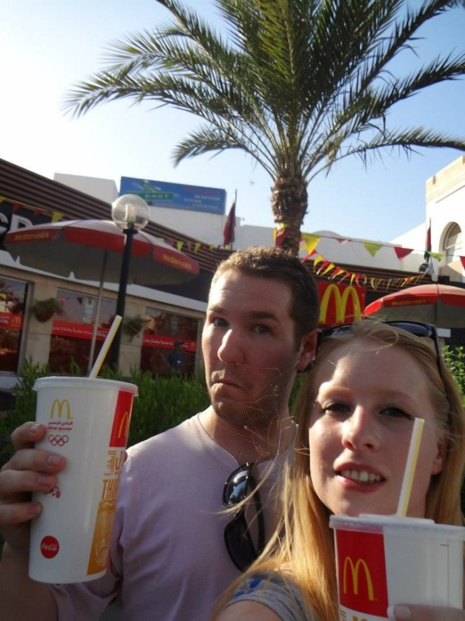 Rosie and Karl outside a McDonald's holding a drink each in Aqaba, Jordan