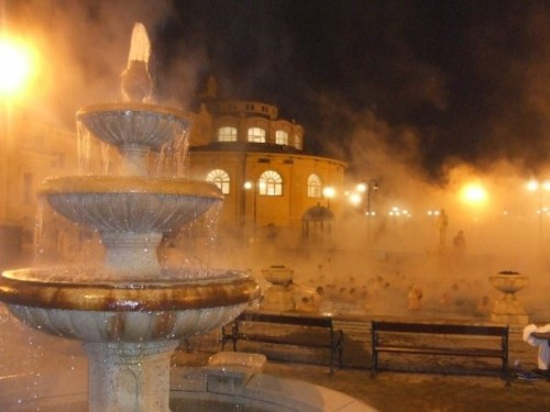 Photo of a 3 tiered water fountain in front of a large steaming pool at the Széchenyi Baths at night
